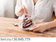 Купить «woman taking cherry from piece of chocolate cake», фото № 30845779, снято 21 мая 2015 г. (c) Syda Productions / Фотобанк Лори