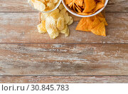 Купить «close up of potato crisps and nachos in bowls», фото № 30845783, снято 22 мая 2015 г. (c) Syda Productions / Фотобанк Лори