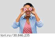 Купить «happy african american woman with eyes of donuts», фото № 30846235, снято 2 марта 2019 г. (c) Syda Productions / Фотобанк Лори