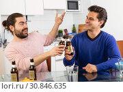 Купить «Best friends talk and drink beer in the kitchen», фото № 30846635, снято 13 марта 2019 г. (c) Яков Филимонов / Фотобанк Лори