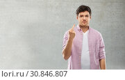 Купить «man showing middle finger over grey concrete wall», фото № 30846807, снято 3 февраля 2019 г. (c) Syda Productions / Фотобанк Лори