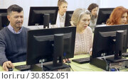 Купить «Group of smiling students of different ages looking together at monitor during computer classes for adults», видеоролик № 30852051, снято 26 февраля 2019 г. (c) Яков Филимонов / Фотобанк Лори