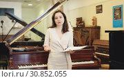 Купить «Female assistant or customer at piano music store», видеоролик № 30852055, снято 12 мая 2019 г. (c) Яков Филимонов / Фотобанк Лори