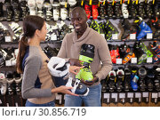 Купить «Adult woman helping African guy choose ski boots», фото № 30856719, снято 16 апреля 2019 г. (c) Яков Филимонов / Фотобанк Лори