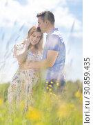 Купить «Young happy pregnant couple hugging in nature.», фото № 30859435, снято 1 июня 2019 г. (c) Matej Kastelic / Фотобанк Лори