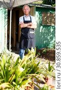 Купить «Serious gardener near garden shed», фото № 30859535, снято 13 июня 2018 г. (c) Яков Филимонов / Фотобанк Лори