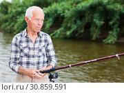 Купить «Mature man angling at riverside», фото № 30859591, снято 10 июня 2018 г. (c) Яков Филимонов / Фотобанк Лори