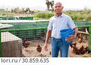Купить «Farmer feeding chikens in a hen house», фото № 30859635, снято 15 мая 2019 г. (c) Яков Филимонов / Фотобанк Лори