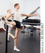 Купить «Choreographer woman and young man do exercises at ballet bar in hall with mirror», фото № 30859867, снято 26 апреля 2019 г. (c) Яков Филимонов / Фотобанк Лори