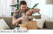 Купить «smiling man unpacking takeaway food at home», видеоролик № 30860047, снято 24 мая 2019 г. (c) Syda Productions / Фотобанк Лори