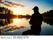 Купить «sunset fishing. fisher with spinning rod», фото № 30860579, снято 8 мая 2019 г. (c) Дмитрий Калиновский / Фотобанк Лори