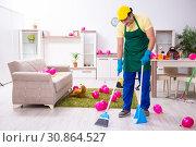 Купить «Young male contractor doing housework after party», фото № 30864527, снято 14 марта 2019 г. (c) Elnur / Фотобанк Лори