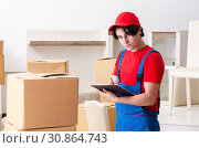 Купить «Young male contractor with boxes working indoors», фото № 30864743, снято 1 февраля 2019 г. (c) Elnur / Фотобанк Лори