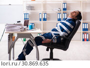 Купить «Young tied male employee in the office», фото № 30869635, снято 18 декабря 2018 г. (c) Elnur / Фотобанк Лори
