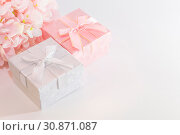 Festive background for a greeting card with a pink and silver gift box with a bow and flowers of artificial hydrangea in pastel colors on a white background with copy space. Стоковое фото, фотограф Светлана Евграфова / Фотобанк Лори