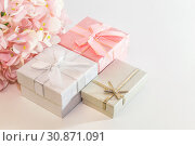 Купить «Festive background with gift wrap with pink, silver, gray boxes with bow and flowers of artificial hydrangea in pastel colors on a white background with copy space», фото № 30871091, снято 2 июня 2019 г. (c) Светлана Евграфова / Фотобанк Лори