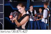 Купить «Smiling girl with laser pistol and playing laser tag with her friends», фото № 30871427, снято 27 августа 2018 г. (c) Яков Филимонов / Фотобанк Лори