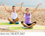 Купить «Cross-legged couple practice yoga on beach in morning», фото № 30871567, снято 19 июля 2019 г. (c) Яков Филимонов / Фотобанк Лори