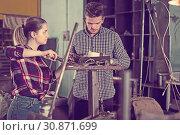 Купить «Nice man training female to repairing drill», фото № 30871699, снято 10 октября 2017 г. (c) Яков Филимонов / Фотобанк Лори