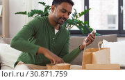Купить «indian man checking takeaway food order at home», видеоролик № 30871759, снято 27 мая 2019 г. (c) Syda Productions / Фотобанк Лори