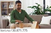 Купить «smiling indian man unpacking takeaway food at home», видеоролик № 30871775, снято 27 мая 2019 г. (c) Syda Productions / Фотобанк Лори