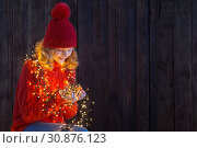 Купить «girl in red hat with christmas light on wooden background», фото № 30876123, снято 7 января 2019 г. (c) Майя Крученкова / Фотобанк Лори