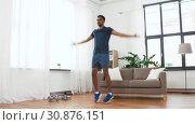 Купить «indian man doing jumping jack exercise at home», видеоролик № 30876151, снято 27 мая 2019 г. (c) Syda Productions / Фотобанк Лори