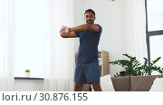 Купить «man with fitness tracker stretching waist at home», видеоролик № 30876155, снято 27 мая 2019 г. (c) Syda Productions / Фотобанк Лори
