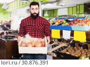 Купить «Smiling man seller showing pomegranates», фото № 30876391, снято 15 ноября 2016 г. (c) Яков Филимонов / Фотобанк Лори