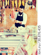 Купить «Male seller offering delicious sausages», фото № 30876435, снято 16 ноября 2016 г. (c) Яков Филимонов / Фотобанк Лори