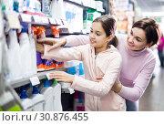 Купить «Woman with girl looking for cleaners in supermarket», фото № 30876455, снято 5 января 2017 г. (c) Яков Филимонов / Фотобанк Лори