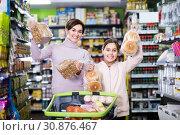 Купить «cheerful woman with daughter choosing bread in supermarket», фото № 30876467, снято 5 января 2017 г. (c) Яков Филимонов / Фотобанк Лори