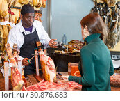 Купить «Seller in butcher shop, cutting jamon for female customer», фото № 30876683, снято 9 января 2019 г. (c) Яков Филимонов / Фотобанк Лори
