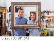 Купить «portrait of man and boy choosing tight wooden bar in picture framing atelier», фото № 30881643, снято 17 мая 2017 г. (c) Яков Филимонов / Фотобанк Лори