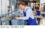 Купить «Craftsman working on glass beveling machine», фото № 30881727, снято 10 сентября 2018 г. (c) Яков Филимонов / Фотобанк Лори
