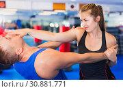 Купить «Woman is training with man on the self-defense course in gym.», фото № 30881771, снято 21 августа 2017 г. (c) Яков Филимонов / Фотобанк Лори