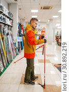 Man at the showcase choosing ski poles, shopping. Стоковое фото, фотограф Tryapitsyn Sergiy / Фотобанк Лори