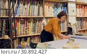 Купить «Experienced saleswoman arranging fabric bolts in textile shop, preparing for sale», видеоролик № 30892427, снято 22 февраля 2019 г. (c) Яков Филимонов / Фотобанк Лори