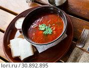 Купить «Ukrainian borscht red-beet soup on bowl, served with bread and salo», фото № 30892895, снято 27 июня 2019 г. (c) Яков Филимонов / Фотобанк Лори