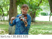 Купить «The young Russian woman with a violin costs at a tree in the park in the summer», фото № 30893535, снято 1 июня 2019 г. (c) Землянникова Вероника / Фотобанк Лори