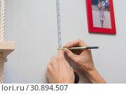 Купить «Руки размечают на стене расположение рамок с фотографиями», фото № 30894507, снято 27 января 2019 г. (c) Иванов Алексей / Фотобанк Лори
