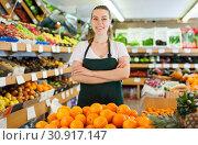 Купить «Smiling woman seller wearing apron standing near fresh oranges», фото № 30917147, снято 27 апреля 2019 г. (c) Яков Филимонов / Фотобанк Лори