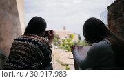 Купить «Two women sit by the stairs one of them draws. Then another woman gets a photo camera.», видеоролик № 30917983, снято 6 июня 2020 г. (c) Константин Шишкин / Фотобанк Лори