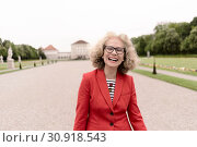 Happy senior woman (67 years old) laughing in park at touristic sight Nymphenburg palace, in Munich, Germany. Стоковое фото, фотограф Benjamin Egerland / age Fotostock / Фотобанк Лори
