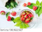Купить «Glass cup of summer tea with fresh strawberry. Green leaves. Fresh mint. White wooden table. Shallow depth of field.», фото № 30922527, снято 5 апреля 2020 г. (c) easy Fotostock / Фотобанк Лори