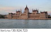 Купить «Beautiful evening view of the Hungarian Parliament Building and the Danube River at sunset in Budapest», видеоролик № 30924723, снято 3 июня 2019 г. (c) Яна Королёва / Фотобанк Лори