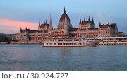 Купить «Beautiful evening view of the Hungarian Parliament Building and the Danube River at sunset in Budapest», видеоролик № 30924727, снято 3 июня 2019 г. (c) Яна Королёва / Фотобанк Лори