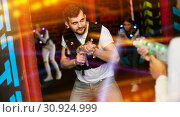 Купить «Excited guy laser tag player in bright beams», фото № 30924999, снято 25 апреля 2018 г. (c) Яков Филимонов / Фотобанк Лори