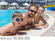 Купить «Family swimming in the outdoor pool at the resort», фото № 30925359, снято 18 июля 2019 г. (c) Светлана Кузнецова / Фотобанк Лори
