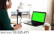 Купить «woman with microphone recording podcast at studio», видеоролик № 30925471, снято 4 апреля 2020 г. (c) Syda Productions / Фотобанк Лори